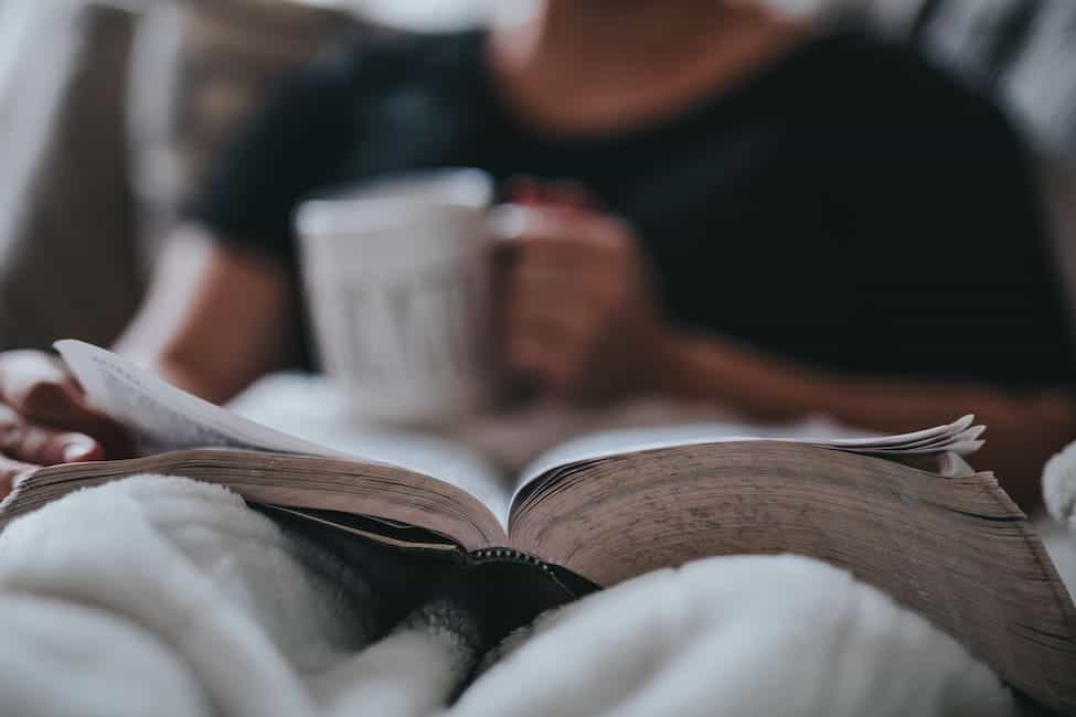 a person sits with a cup of coffee reading a book covered in a blanket
