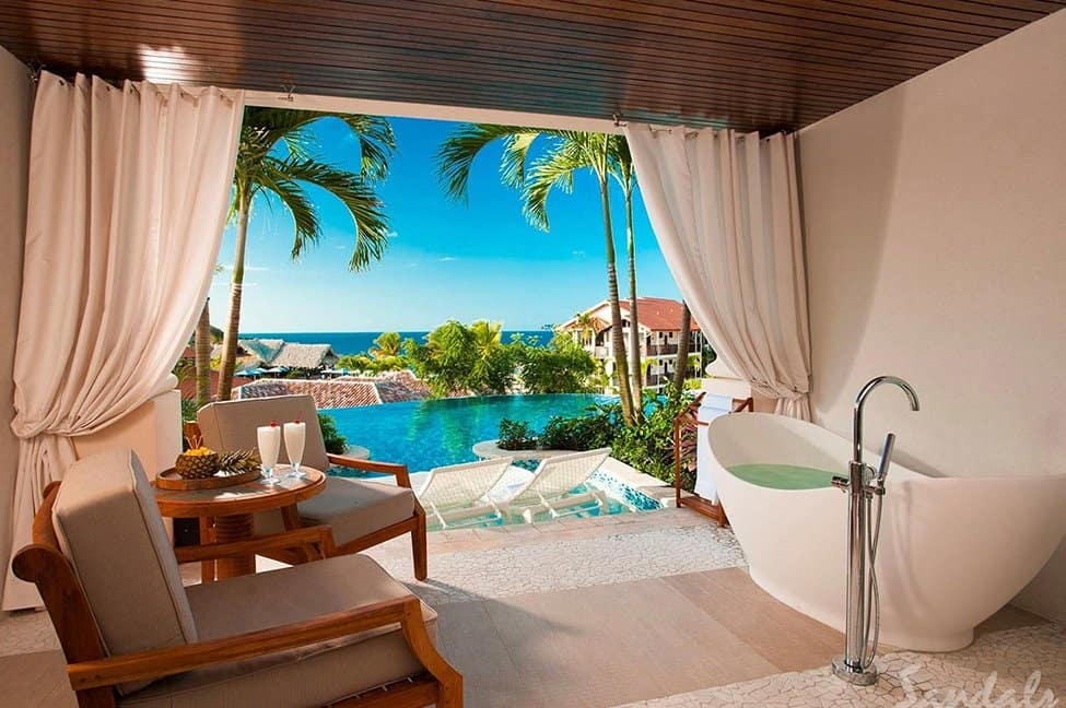 A soaker bathtub overlooking a patio and a Sandals Resort